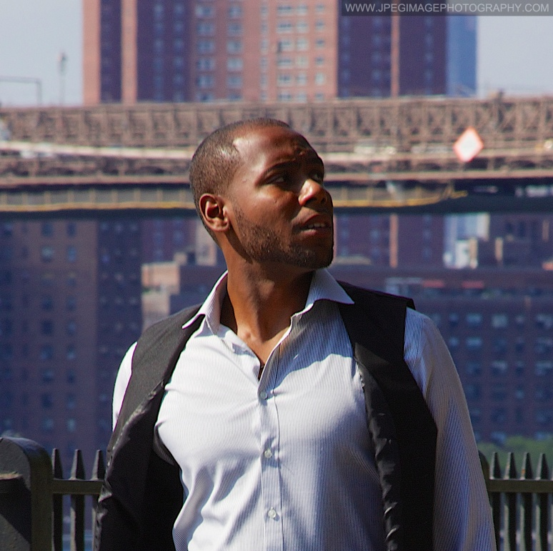 Afro-American male walking down the Brooklyn Heights Promenade, located in Brooklyn Heights, New York while looking to his left.