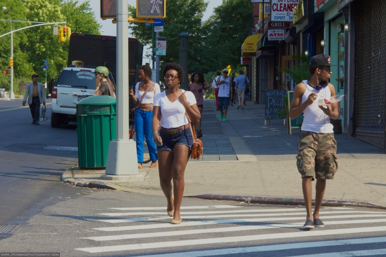 Two people walking down Fulton Street and South Portland Avenue in Fort Greene Brooklyn, New York City.