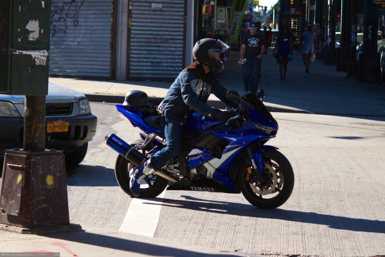 Person on Yamaha motorcycle crossing a Brooklyn street across Broadway.