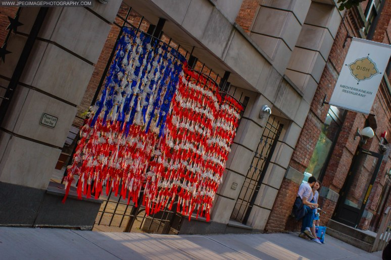 Tassels hanging on a gate made to look as the flag of the United States, as an artist work is shown during the DUMBO Arts Festival located on Washington Street in DUMBO Brooklyn, Sunday September 29, 2013.
