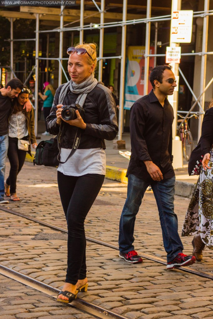 Woman walking around taking photos of the DUMBO Arts Festival located in DUMBO Brooklyn, Sunday September 29, 2013.