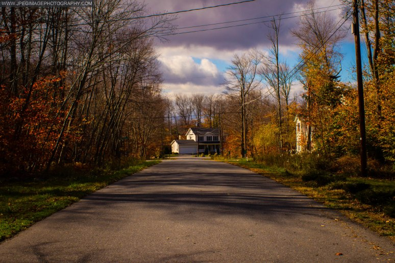 Large house at the end of a road under cloudy sky.