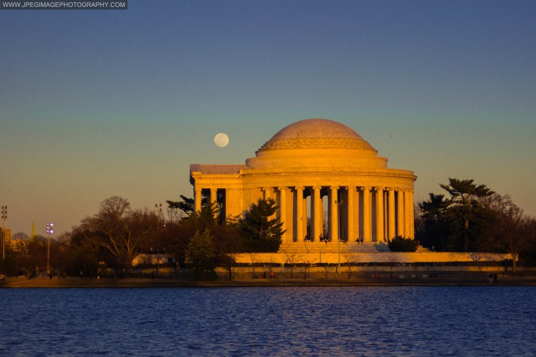 Jefferson Memorial building in Washington DC during golden hour/dusk with full moon rising.
