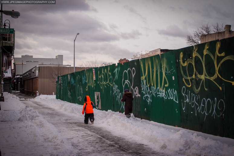 Woman and child walking in the snow along Broadway in Bedford Stuyvesant, Brooklyn New York.