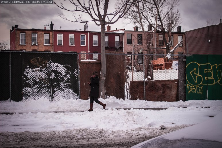 Woman walking down a local snow covered street in Bedford Stuyvesant, Brooklyn New York.