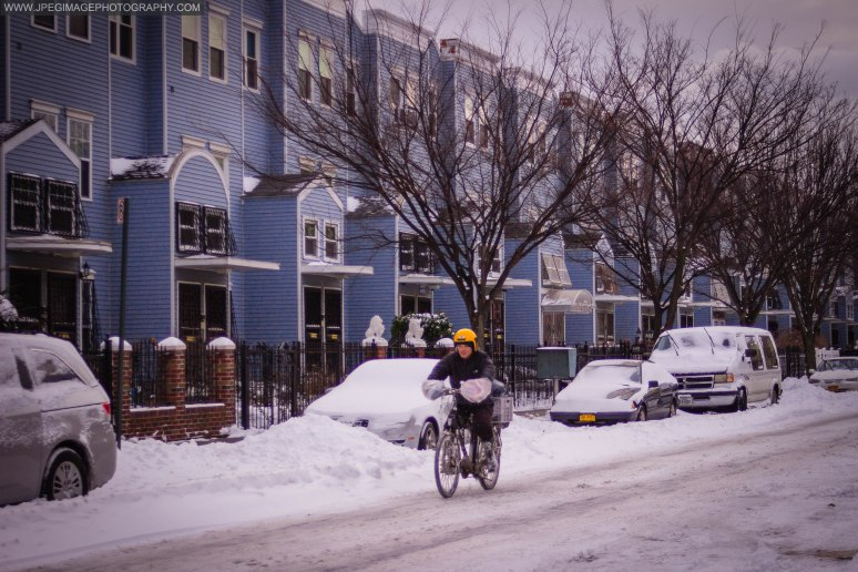 Local delivery person on a bicycle riding on a snow covered street in Bedford Stuyvesant, Brooklyn New York.